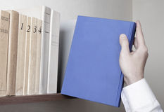 Bookshelf and blue book Royalty Free Stock Images