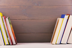 Bookshelf with books on wooden plank wall Stock Photos
