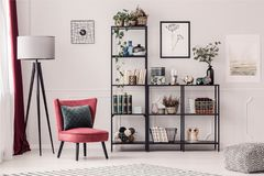 Bookshelf in living room. Black, metal bookshelf, lamp and red armchair in living room interior royalty free stock image