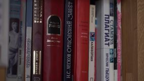 Bookshelf. Old books on a wooden shelf. Many old books on bookshelf in library stock footage