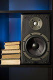 Bookshelf speaker and books. Books and speaker on bookshelf with blue background Royalty Free Stock Image