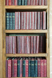 Bookshelf with Vintage Books. Wooden bookshelf containing old leatherbound prayer books Royalty Free Stock Photo