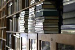 Bookshelves piled with books Stock Image