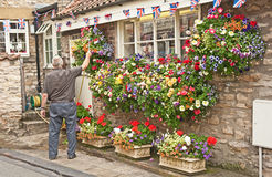 Bookshop in Helmsley, Yorkshire. Flowers decorating a book shop also displaying Jubilee flags at Helmsley, East Yorkshire being watered Royalty Free Stock Images