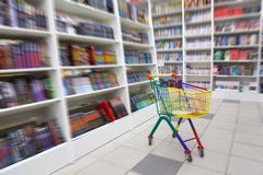 Bookshop interior. A in front of racks with books there is bright cart for purchases Royalty Free Stock Photography