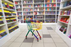 Bookshop interior. Before racks with books there is bright cart for purchases. Blurred Royalty Free Stock Photo