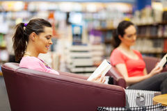 Bookstore. Young women reading book in bookstore royalty free stock images