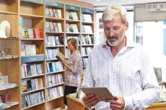 Male Bookstore Owner Using Digital Tablet With Customer In Background royalty free stock image