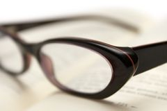 Bookworm. Glasses on an open book. Shallow depth of field Stock Image