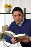 Bookworm. A man leaning on a bookshelf and reading a book Stock Images