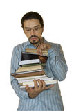 Bookworm. Young latino man looking for a book in the stack that he's holding. White background Royalty Free Stock Images