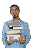 Bookworm. Young latino man rolling his eyes, holding a stack of books. White background Stock Photography