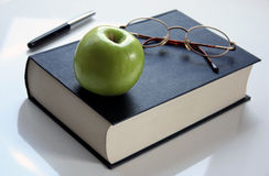 Bookworm. Reference book with spectacles and apple stock photography