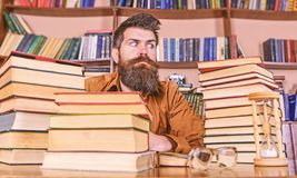 Bookworm concept. Man on strict face sit between piles of books, while studying in library, bookshelves on background. Teacher or student with beard sit at stock photography