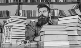 Bookworm concept. Man on strict face sit between piles of books, while studying in library, bookshelves on background. Teacher or student with beard sit at royalty free stock photography