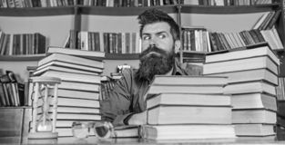 Bookworm concept. Teacher or student with beard sit at table with hourglass and glasses, defocused. Man on strict face. Sit between piles of books, while stock images