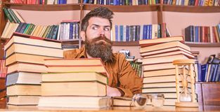 Bookworm concept. Teacher or student with beard sit at table with hourglass and glasses, defocused. Man on strict face. Bookworm concept. Teacher or student with royalty free stock photos
