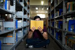 Bookworm. Male student holding book in front of his face and reading Stock Image