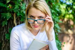 Bookworm student relaxing with book green nature background. Girl keen on book keep reading. Cute bookworm in eyeglasses. Enjoy every chapter. Woman blonde take royalty free stock photo