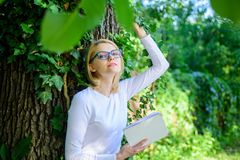 Bookworm student relaxing with book green nature background. Girl keen on book keep reading. Woman blonde take break. Relaxing in park reading book. Literature stock photo