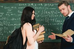 Bookworm. Woman student in glasses with book stack and backpack stand with teacher man on chalkboard in classroom. More. Bookworm. Woman student in glasses with royalty free stock photos