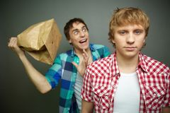 Boom. Crazy guy being ready to explode paper bag behind his friend back Royalty Free Stock Photos