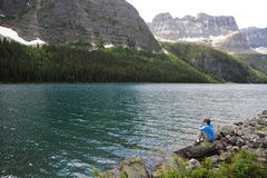 Boom Lake, Canada. A tourist sitting at the bank of the Boom Lake in Banff National Park, Canada Royalty Free Stock Photo