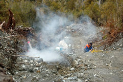 Boom. Man blows up a 4 metre deep charge for seismic test, Westland, New Zealand. Smoke emerges from the blast site Stock Photography