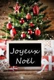 Boom met Joyeux Noel Means Merry Christmas stock afbeeldingen