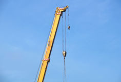 Boom of mobile crane with blue sky background. Stock Photos
