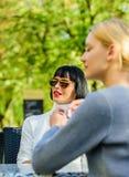 Boom op gebied de modieuze vriendenmeisjes komen in koffie samen Vrouwelijke frienship Ontspan met koffie De Schoonheid van de ma royalty-vrije stock foto