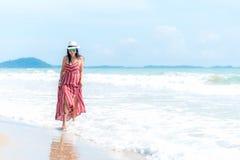 Boom op gebied Glimlachende vrouw die de manierzomer dragen die op het zandige oceaanstrand lopen royalty-vrije stock fotografie
