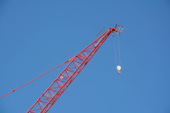 Boom rouge de grue contre un ciel bleu Photographie stock libre de droits