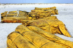 Boom on white sand beach for oil cleanup stock photography