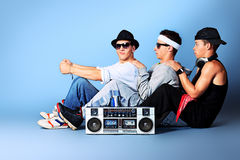 Boombox fun. Group of trendy teenagers posing with boombox at studio stock photos