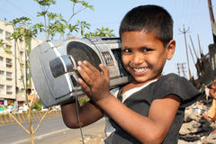 Boombox Kid. A streetside Indian kid carrying is favorite possession - The music Boombox stock photo