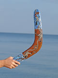 Boomerang in womens hand against of the blue sea. Stock Photos