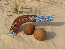 Boomerang and coconuts. Colorful boomerang and coconuts on a sand Royalty Free Stock Photo