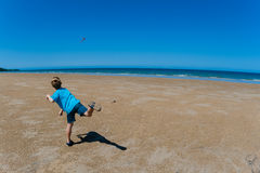 Boomerang Flying  Boy Beach. Young male boy dressed in blue shirt and shorts and sandals throwing a boomerang on wide flat beach with the distant calm sea ocean Stock Images