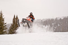 Boondocking in the Big Horns. Rider Jumping a Snowmobile at the crest of a hill covered in deep powder, with tree-covered mountains in the background Stock Photo