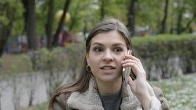 Boos Aantrekkelijk meisje dat emotioneel op de telefoon op de aard in het stadspark spreekt stock videobeelden