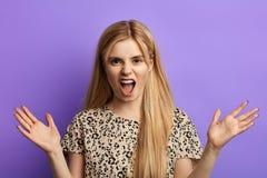 Boos die blondemeisje met handen het schreeuwen bij camera worden opgeheven stock afbeelding