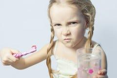Boos en furio?s meisje niet bereid om haar tanden te borstelen royalty-vrije stock foto's