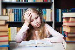 Boos en vermoeid schoolmeisje die met een stapel van boeken bestuderen stock foto