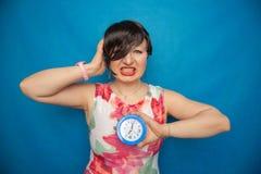 Boos gillend ongelukkig meisje die een ronde wekker op blauwe studioachtergrond houden stock afbeeldingen
