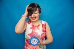 Boos gillend ongelukkig meisje die een ronde wekker op blauwe studioachtergrond houden royalty-vrije stock afbeeldingen