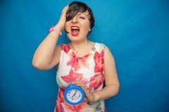 Boos gillend ongelukkig meisje die een ronde wekker op blauwe studioachtergrond houden royalty-vrije stock afbeelding