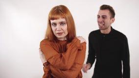 Boos jong mannetje die bij zijn meisje en golvende handen schreeuwen De verstoorde vrouw is vermoeid van kerelsagressie en dicht  stock videobeelden