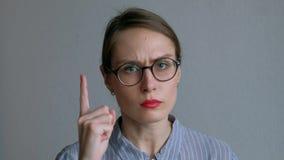 Boos jong meisje die in glazen haar vinger richten Op witte achtergrond stock video