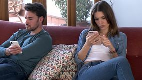 Boos jong paar die elkaar negeren die telefoon na een argument met behulp van terwijl thuis het zitten op bank stock footage